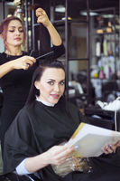 Professional hairdresser preparing to give a haircut to her beautiful cheerful female client combing her hair