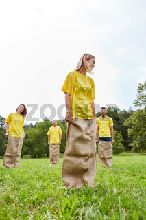 Sportliche Mannschaft beim Sackhüpfen