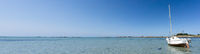 very wide panorama ocean coast and beach landscape with small sailboat under a blue sky at low tide