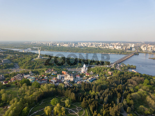 Aerial view beautiful panorama of the city of Kiev, a botanical garden and the Dnieper river against the blue sky