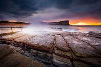 Sunrise sky and waves crash onto rocky beach shore