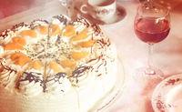 Teil einer Kaffeetafel mit Mandarinen-Sahne-Torte, Roséweinglas und Geschirr