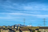 Homes on a hill with electricity towers and snow covered mountain background