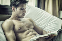 Young man shirtless on his bed reading a book