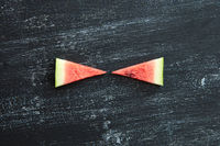 Two triangular pieces of fresh watermelon on a black concrete background with copy space. Summer vitamin dessert. Flat lay
