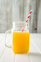 Orange juice in jug with swirly straw.