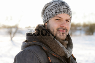 Young man smiling in a winter scene landscape. Christmas and winter wear concept.