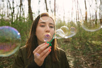 Young woman blowing soap bubbles in the woods.