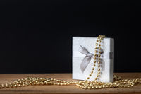 Holidays decoration gift box with golden perls on black background