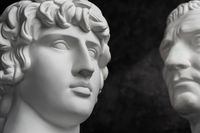 Gypsum copy of ancient statue Augustus and Antinous head on dark textured background. Plaster sculpture mans face.