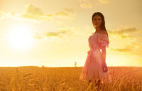 Young girl in wheat field at sunset