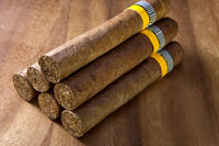 rolled cigars from a tobacco leaf on a wooden background