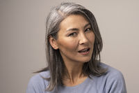 Pensive Adult Woman of Mongolian Nationality with Gray Hair on a Gray Background.