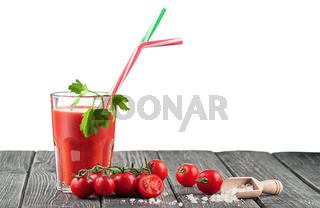 Glass of tomato juice on a wooden table