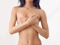 Frau im mittleren Alter tastet ihre Brust ab