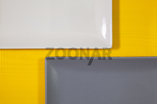 White and gray rectangle plates on the yellow  wooden table.