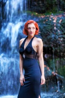 Junge Frau steht vor einem Wasserfall