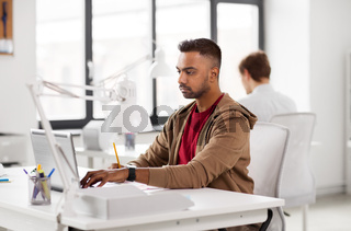 indian man with laptop computer at office