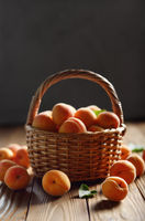 Wicker basket with ripe apricots on wooden table