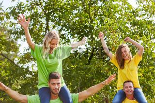 Glückliche junge Leute beim huckepack Spiel