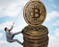 Businessman climbing the stack of bitcoins