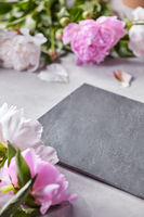 Slate board decorated with petals and pink flowers of peonies on a gray concrete background with copy space. Flower layout