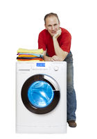 happy man smiling standing next to a new washing machine and a stack of clean laundry