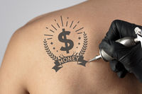 Tattooing money and currency concept on naked back