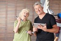 Seniorin macht Hanteltraining im Fitnesscenter
