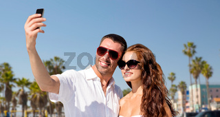 couple in shades making selfie over venice beach