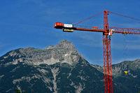 Baukran vor Alpenkulisse