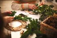 Cropped view of florist hands making Christmas wreath with fir branches
