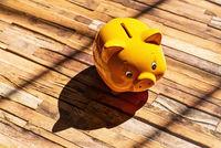 Gelbes Sparschwein wirft einen Schatten