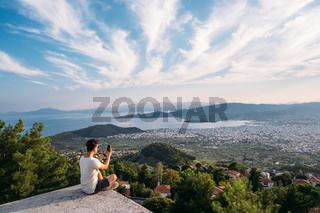 The guy sits on the edge of the roof, in the background is the coastal city.