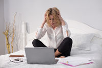 Business woman sitting on bed and working