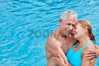 Senioren Paar am Pool umarmt sich liebevoll
