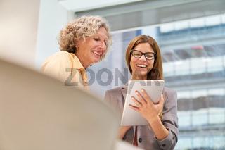 Ältere Business Frau und junge Kollegin mit Tablet