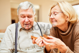 Senioren Paar spielt mit einem Holzpuzzle