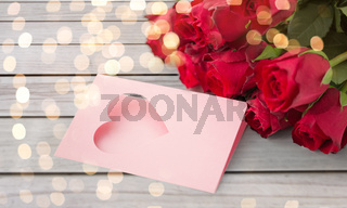 close up of red roses and greeting card with heart