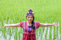 Asian woman in traditional costume for Karen show green rice field