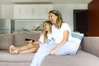 Woman and her little daughter with remote control embracing on sofa