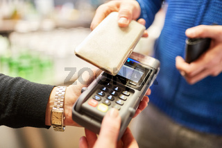 Kunde bezahlt mit Smartphone via NFC am Lesegerät