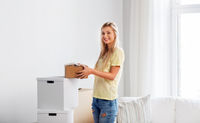 happy woman with boxes moving to new home