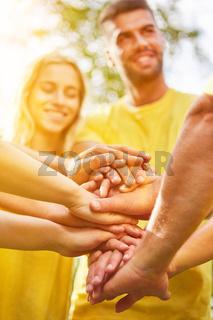 Gruppe stapelt Hände zur Motivation als Team