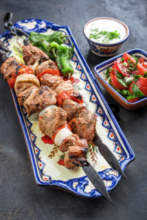 Traditional Greek souvlaki barbecue skewer with tomato onion salad and  tzatziki as closeup on a plate