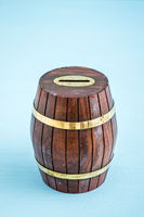 Wooden Barrel Money Box on Blue Background