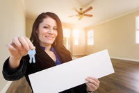 Hispanic Woman With House Keys and Blank Sign In Empty Room of House