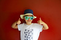Pretty emothional child wear a hat and sunglasses on a red background