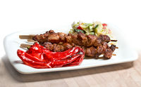 A plate with barbecue, sweet peppers and greens.