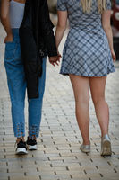 Girlfriends holding hands and walking